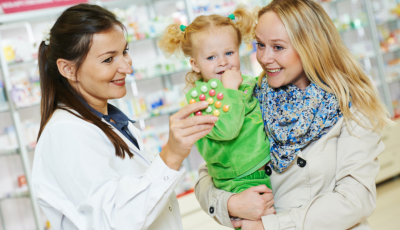 pharmacist holding medicine and mother and her child