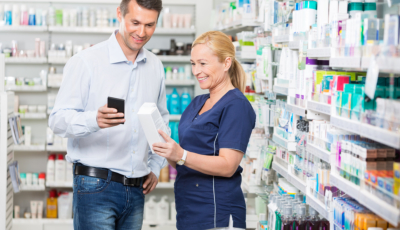 customer using mobile phone while pharmacist holding a product in pharmacy